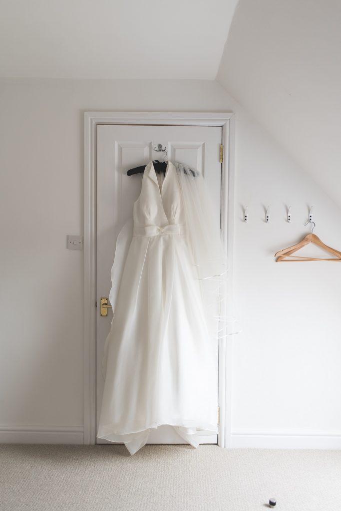 Wedding Investment - White Wedding Dress Hanging On The Door