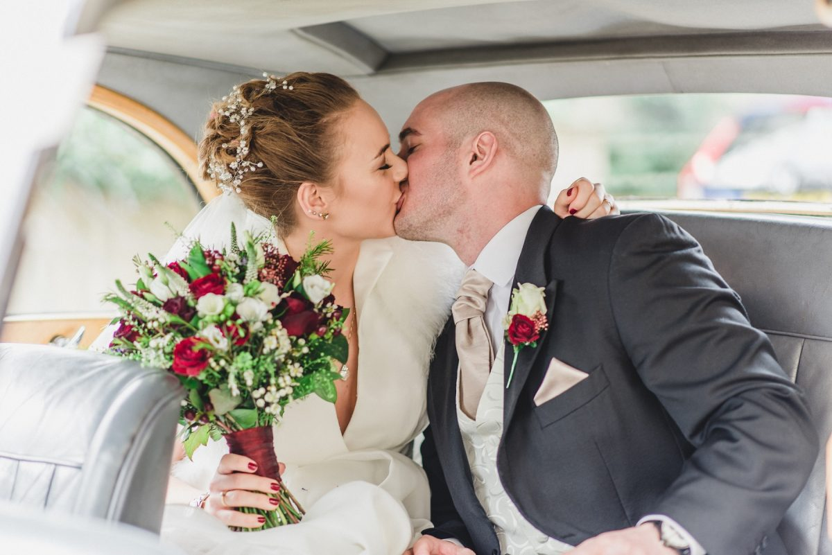 Wedding photographer in Norfolk - Bride and groom kissing inside a Rolls Royce.