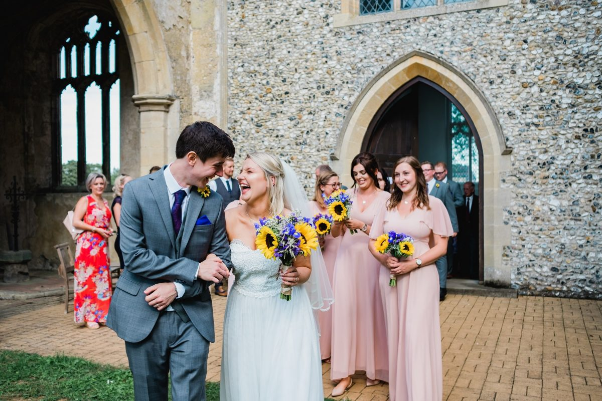 Wedding blog of James Malkin Photography - Bride and groom just married and leaving the church laughing together