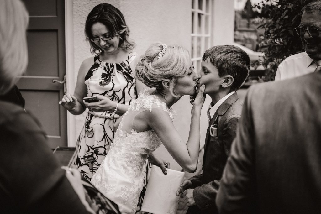 The bride kissing a small boy