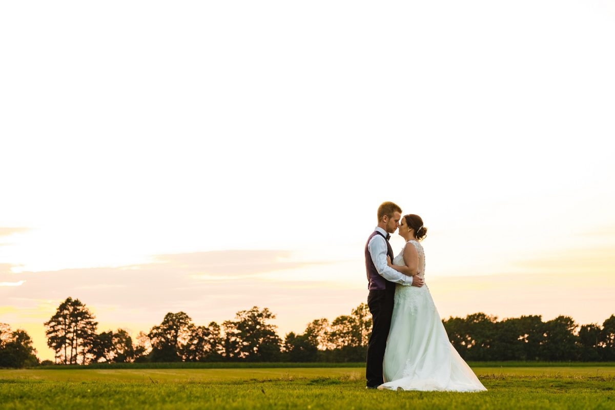 Wedding photographer in Norfolk - Bride and groom hugging during sunset.