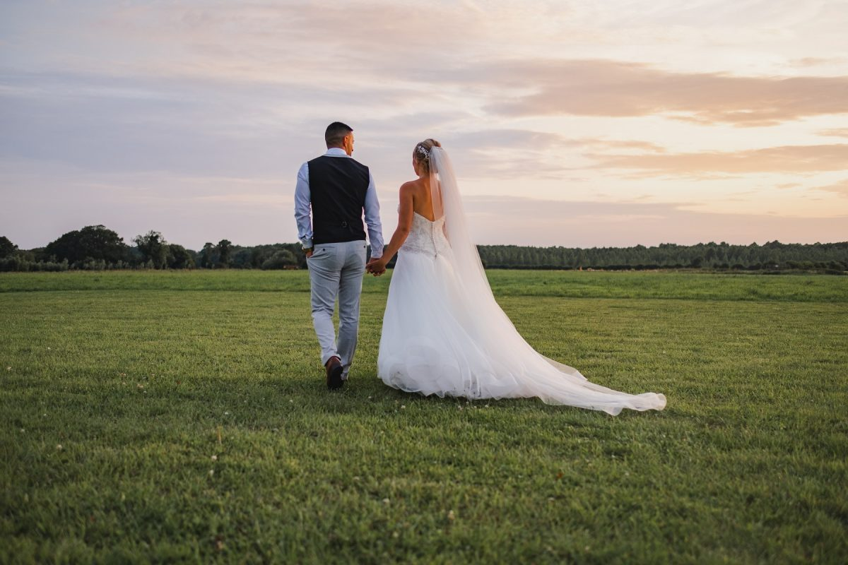 Bride and groom walking together in the fields