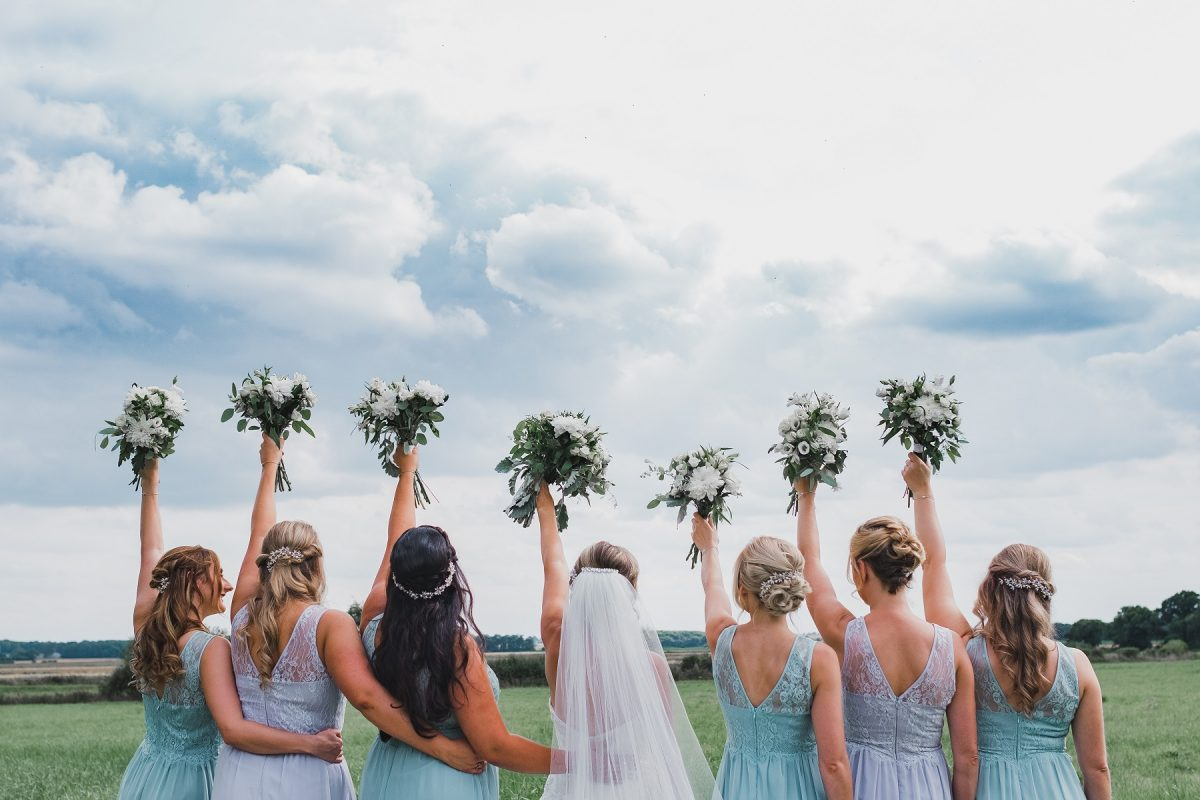 Bridal party holding bouquets in the air