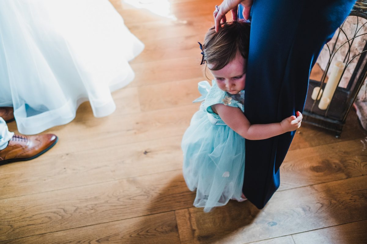 A small girl holding onto mums leg during a wedding ceremony