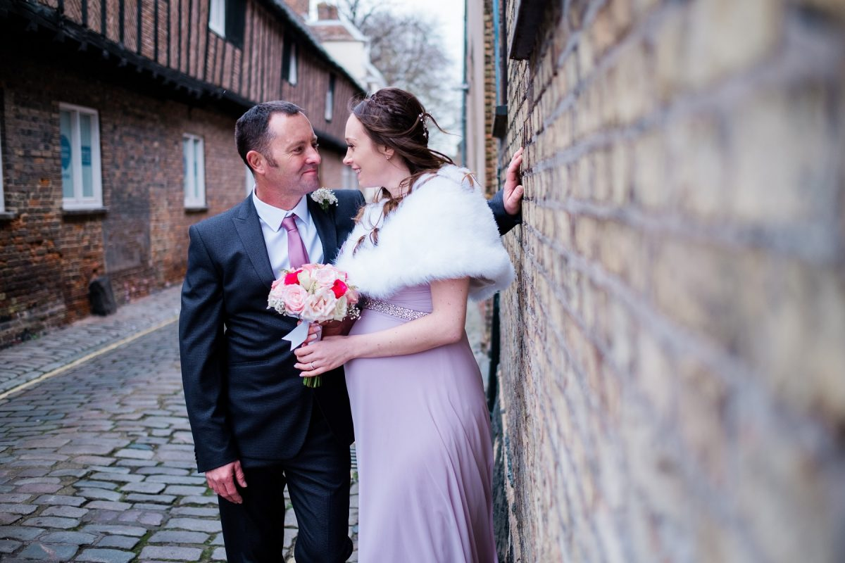 Bride and groom down a cobbled street in Kings Lynn