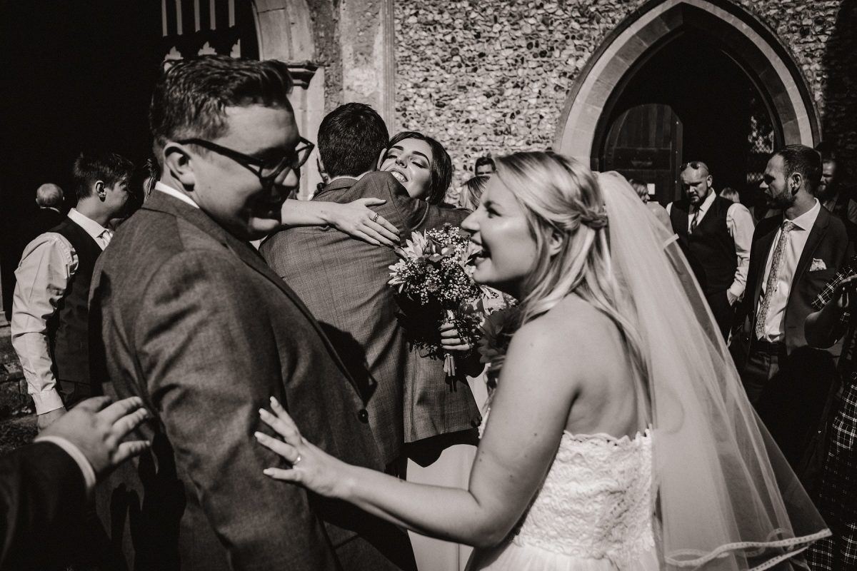 A bridesmaid hugging the groom outside the church