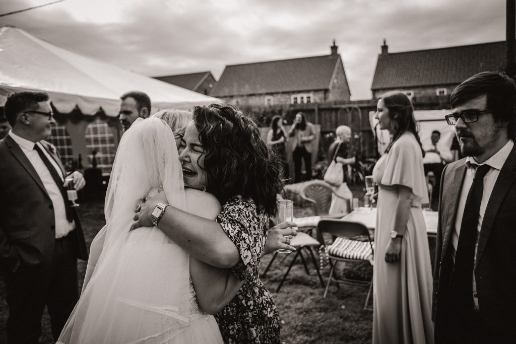 The bride hugging one of her friends at the wedding party