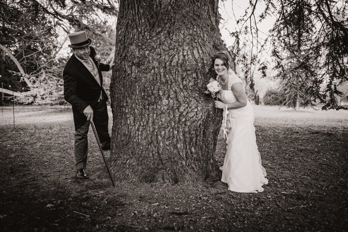 Bride and groom posing near a tree at Mount Amelia