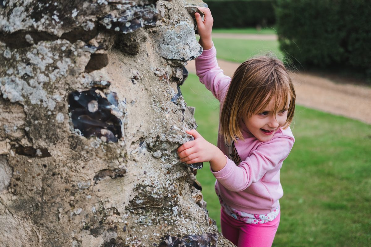 Small girl trying to climb the wall of Pentney Abbey