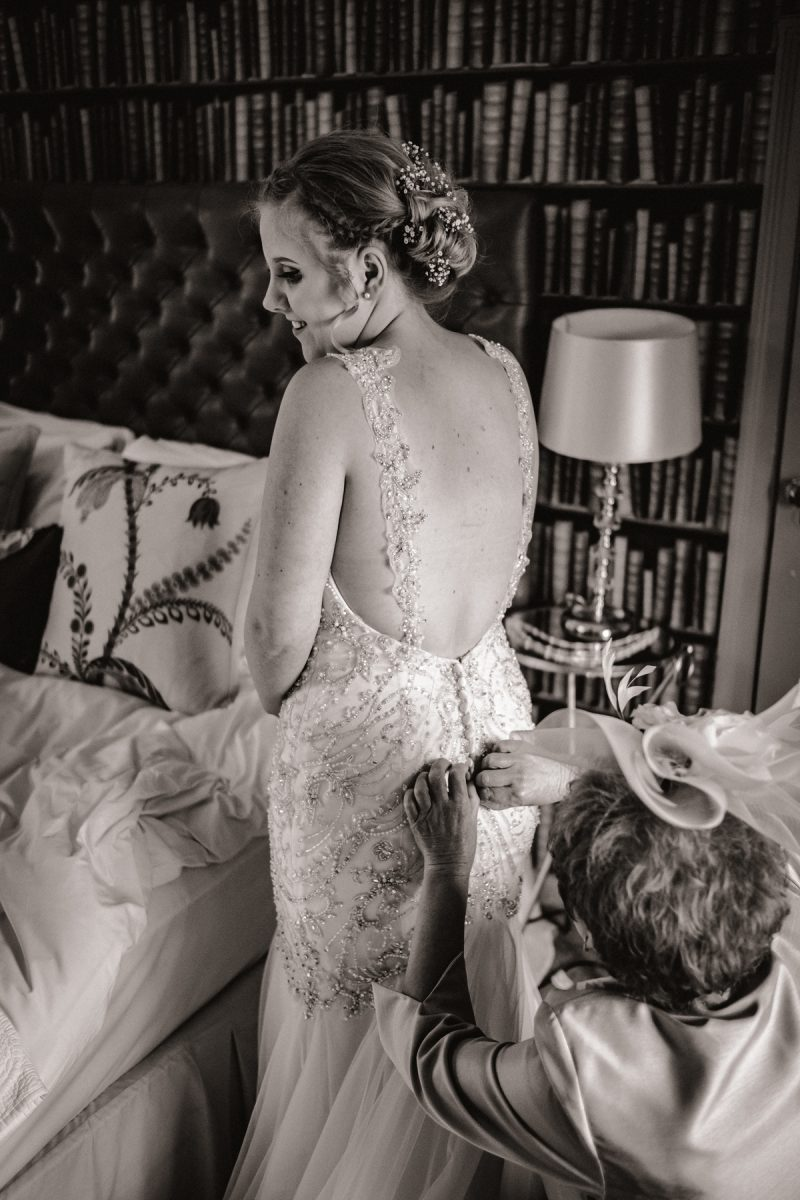 Wedding photographer in Norfolk - Capturing the bride's dress being fastened