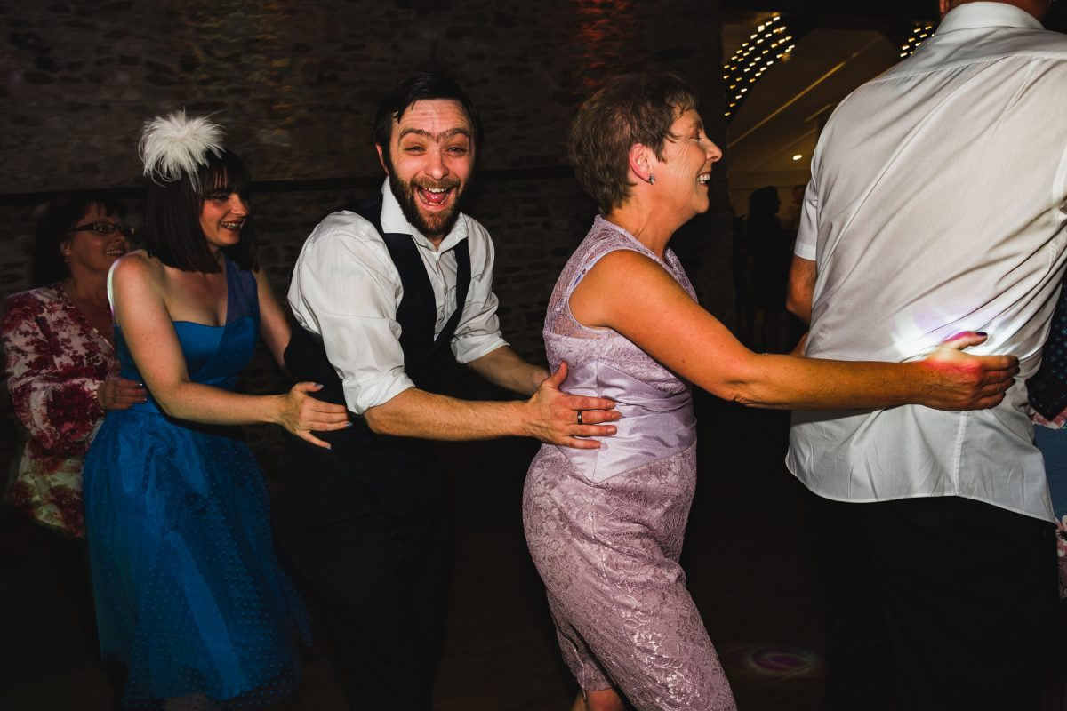 Wedding guests doing the conga at Pentney Abbey