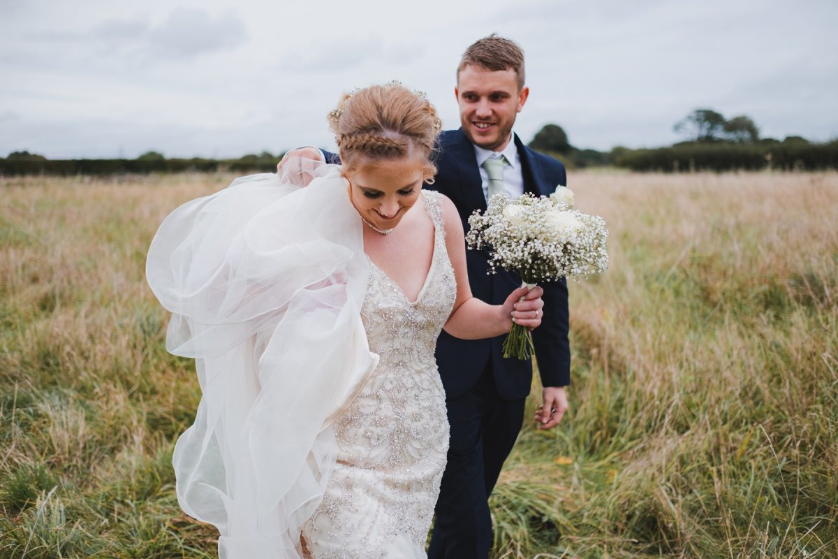 Bride and groom walking in the fields at Pentney Abbey