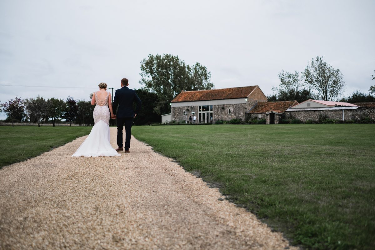 Bride and groom walking towards the barn at Pentney Abbey