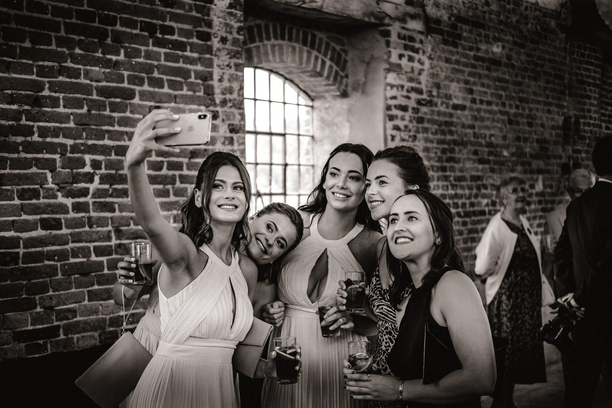 Bridesmaids taking a selfie at Godwick Great Barn