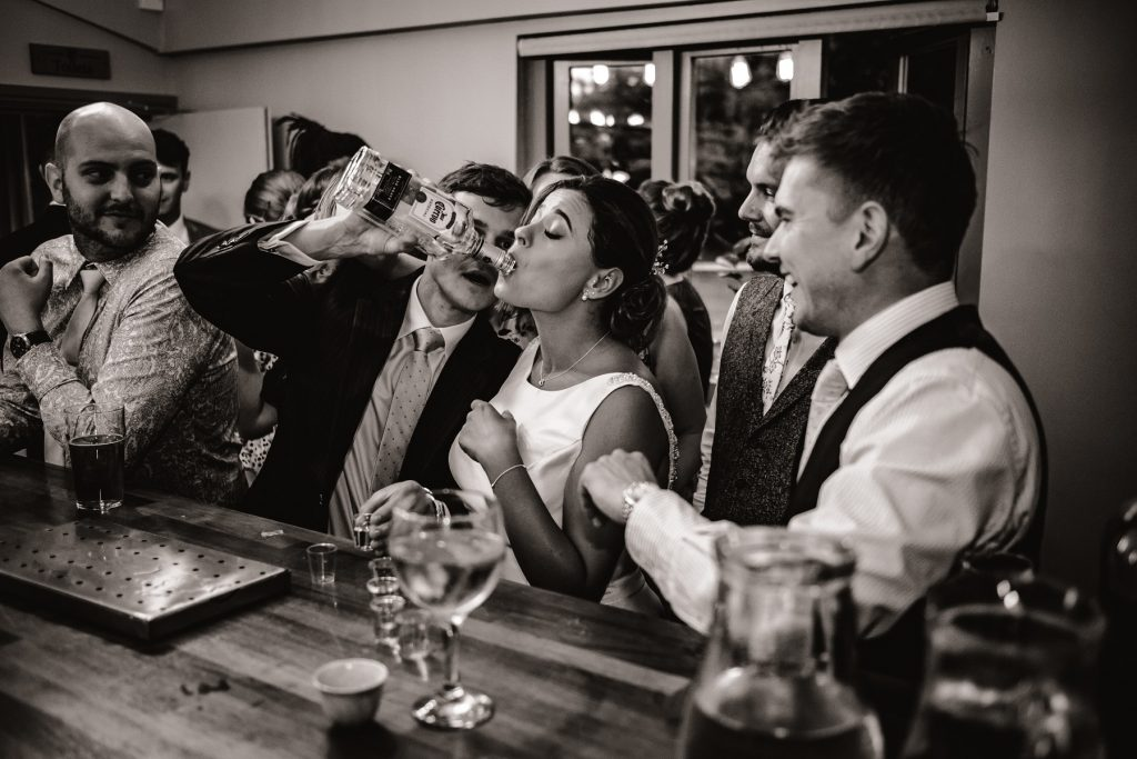 The bride at the bar downing Tequila from the bottle