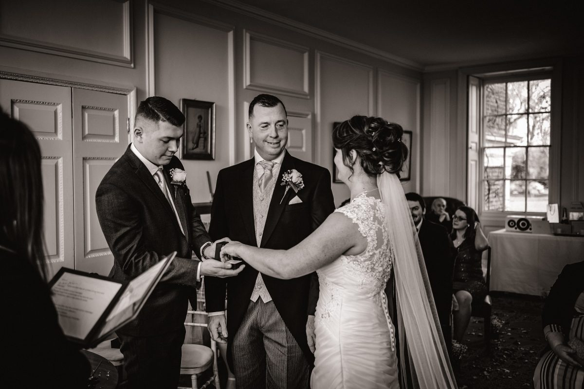 Best man handing the ring to the bride
