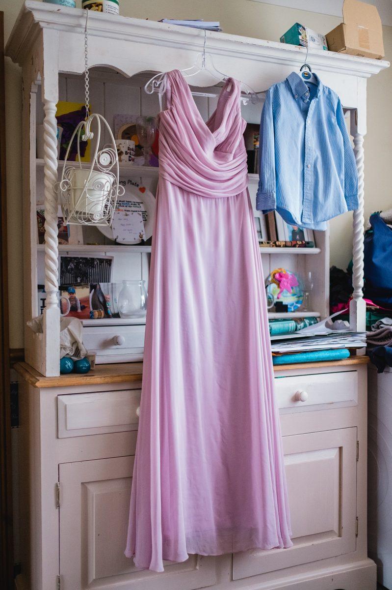 Pink wedding dress hanging on the wooden dresser
